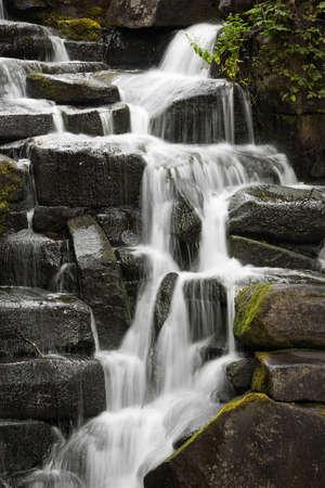 Waterfall flowing over dark rocks long slow exposure