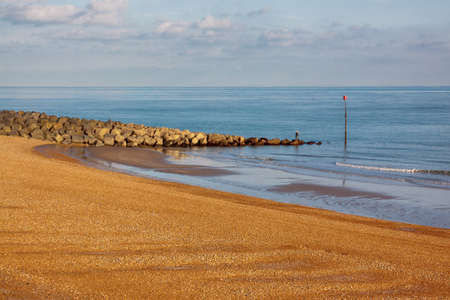 Golden pebble beach and rock groyne blue sea with distant fisherman Stock Photo