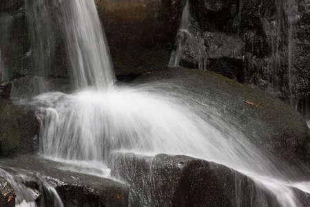 Waterfall over dark rocks long exposure closeup