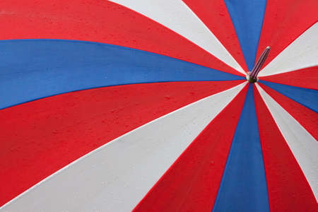 Red white and blue umbrella with rain drops