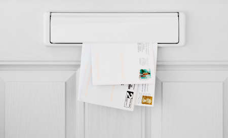 Three letters in a letterbox inside a white front door Stock fotó