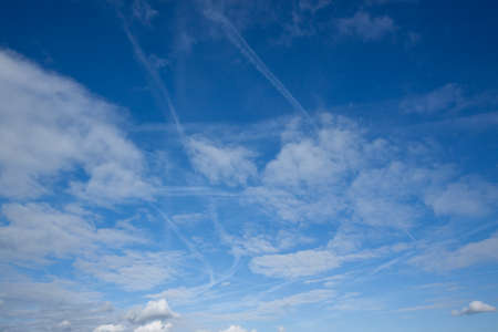 Blue sky with clouds and aircraft vapour trails Stock Photo