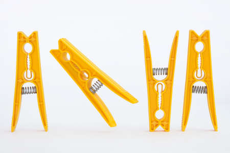For yellow dancing pegs on a white background Standard-Bild