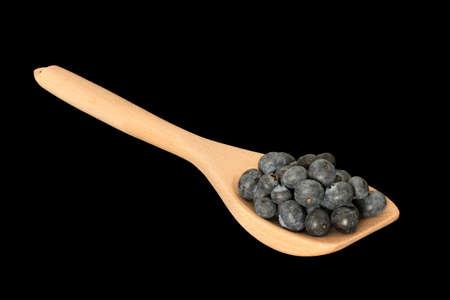 Handfull of blueberries on a wooden spoon isolated on black with clipping mask Stock Photo