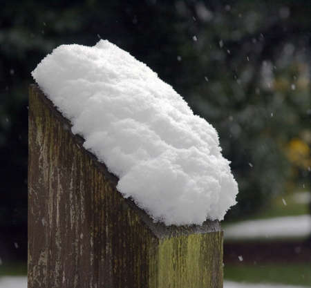 Pile of snow settling on wooden post
