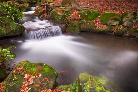 Two small waterfalls in autumn woodland long exposure