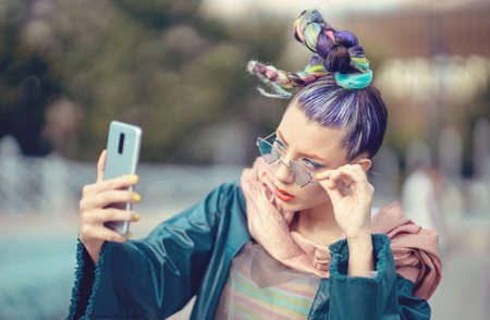 Funky young girl with crazy fashion style hair taking selfie on street