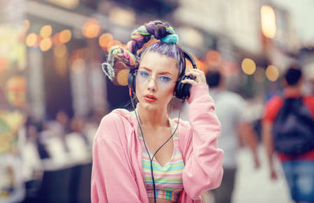 Young nonconformist girl listening music in headphones on the crowded streets.