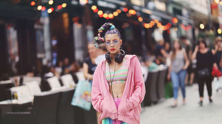 Urban portrait of eccentric young woman model on the streets - Unique-looking younger with colourful hair, accessories and clothes