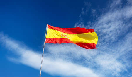 Spanish flag on a pole, undulating in the wind on blue sky with soft white clouds
