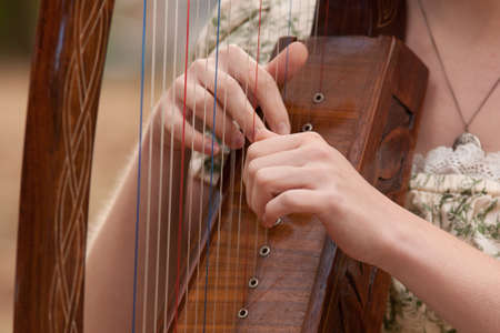 harp: Young woman playing a harp Stock Photo