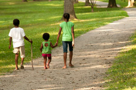 African-American children walking along a gravel path Stock Photo - 14835894