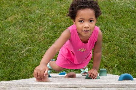 black grip: An African-American toddler climbing a play wall