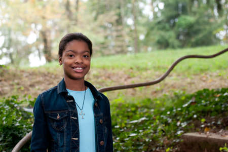 rail cross: An african-american girl standing next to a meadow Stock Photo