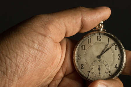 grasp: An African American hand holding an antique pocket watch