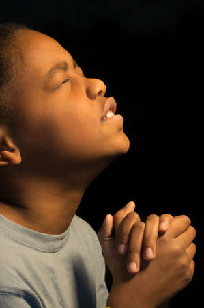 sanctification: A boy fervently prays to God  Stock Photo