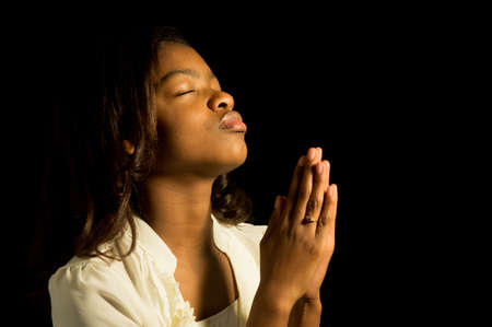 An African American girl prays to God.