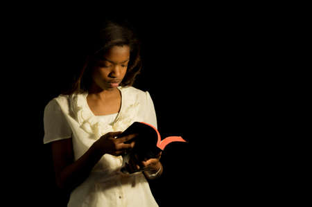 An African American girl reads her Bible. Imagens