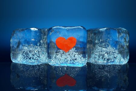 a frozen red heart as a simbol of frozen love, ice cubes with heart photo