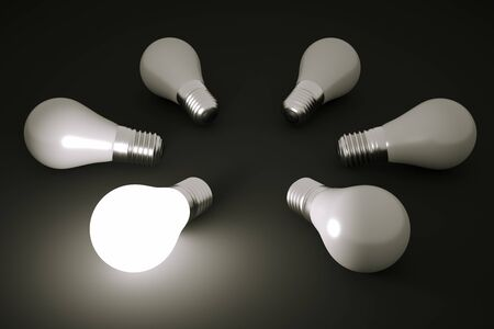 glowing light bulb: a glowing bulb in a darkness Stock Photo