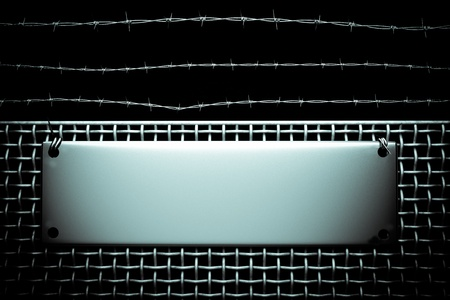 barbwire: a wire fence with  barbed wire and metal board as a background Stock Photo