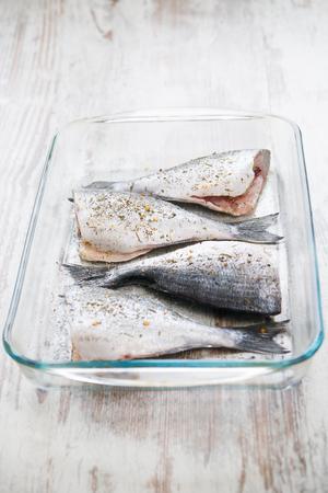 Fresh gilthead Dorado fish in a gless pan on a wood background photo