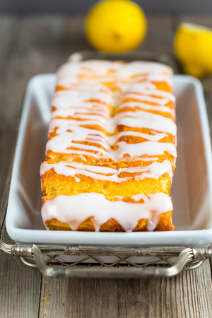drizzle: Lemon yogurt loaf cake, sliced on a creative plate on wooden background for your design Stock Photo