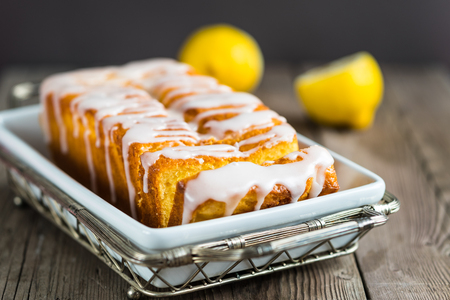 Lemon yogurt loaf cake, sliced on a creative plate on wooden background for your design 스톡 콘텐츠