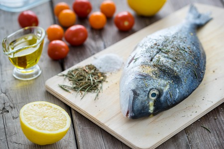 Dorado fish on slate board with cherry tomatoes, lemon, garlic and rosemary. Top view for your design Stock Photo