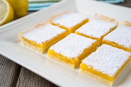 Frisch gebackene Zitronenbarren mit Puderzucker auf einer Schale Standard-Bild - 83941081