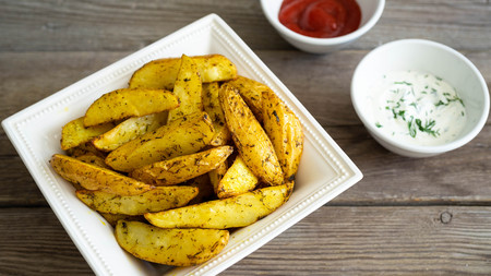 Potato wedges with souce on wooden background