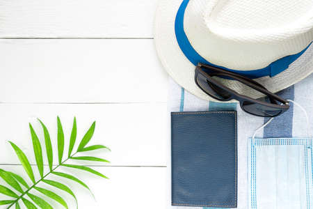 White hat, glasses, passport and medical mask on a white background. 免版税图像