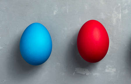 Blue and red Easter eggs on textured gray background. Horizontal orientation. Top view. 版權商用圖片