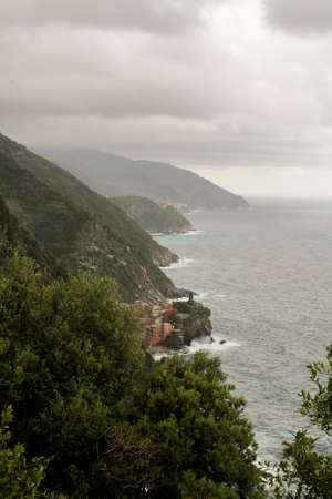 forested: High forested mountains and stormy sea under the low clouds.