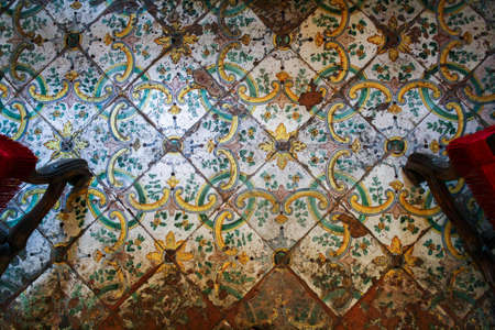Old shabby tiled floor with a beautiful yellow-green ornament on a white field