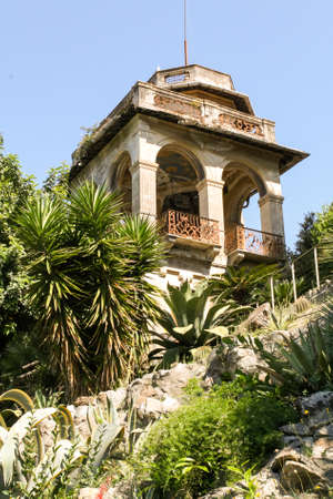 Old abandoned gazebo on a hill among the palm trees in the summer.