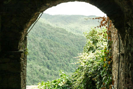 View through the ancient archway in the wooded mountains. Stock Photo
