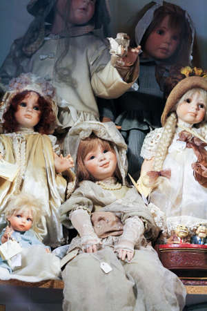 poppet: Vintage porcelain dolls in classical robes in the window of an antique shop. Stock Photo