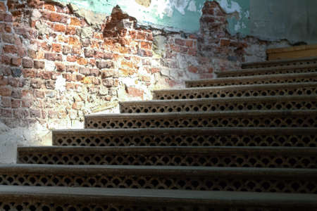 crumbling: Cast-iron openwork stairs and an old brick wall with crumbling plaster Stock Photo