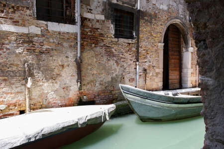 crumbling: Two boats in the narrow channel of water a milky green. Old brick wall with crumbling plaster, arched doorway.