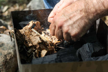 flint: A man lights a fire with a flint. Coal, bright sparkles with smoky tails, dry leaves and twigs. Stock Photo