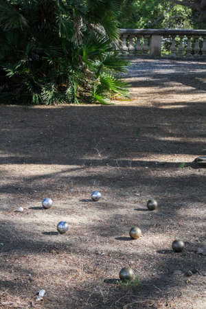 steel balls: Steel balls for a game of boules on the ground among light and shadow in a subtropical park.