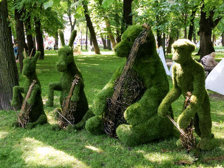 parc: Quartet musicians animals in the form of lawn shrubs. Donkey, monkey and a goat with violins and a double bass bear.