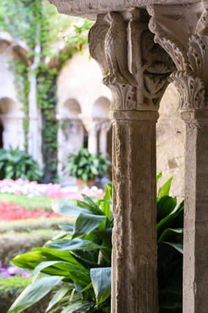 flowerbeds: Old Corinthian columns, green bush and blurred atrium with flowerbeds