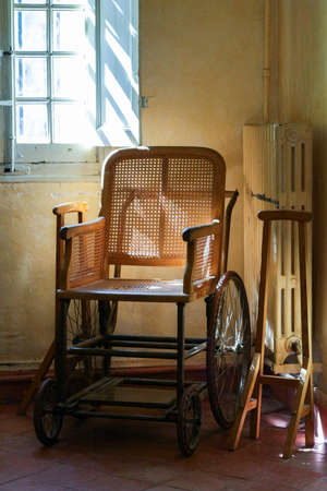 grille: Old wooden wheelchair in the interior. Pale yellow walls, window grille and radiator. Stock Photo