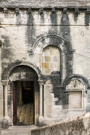 arched: Ancient wall of limestone with arched windows and doors. Windows partially laid stones.
