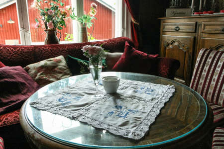 lace doily: Interior of a cozy rustic living room filled with antique furniture. A round wooden coffee table with glass, lace doily, red sofa with lots of pillows, classic carved chest of drawers, window and flower vases. Stock Photo