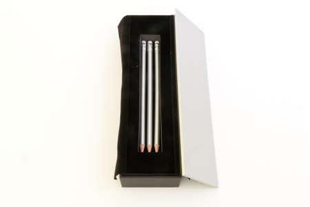 black velvet: Silver pencils in a black velvet box on white background. Stock Photo