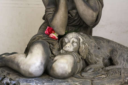 monumental cemetery: Statue of a dog on knees of grieving girl on monumental cemetery of Staglieno in Genoa.