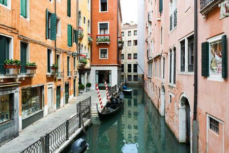 case colorate: Stretto canale veneziano, case colorate e gondola